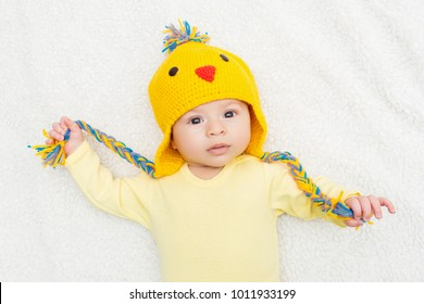 Three months old baby in Easter chicken knitted hat. High angle view, studio lighting, mild retouch, vibrant colors.