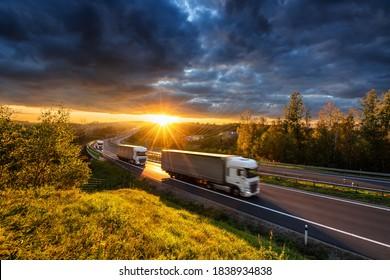 Drei unscharfe LKWs, die auf der Asphaltstraße in bewaldeter Landschaft in den goldenen Strahlen des Sonnenuntergangs mit dunkler Wolke fahren