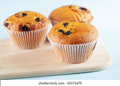 Three muffins with blueberry on a wooden board