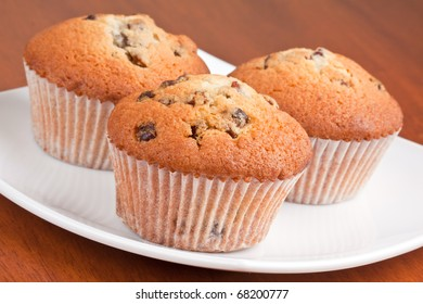 Three muffins on a white plate on the table