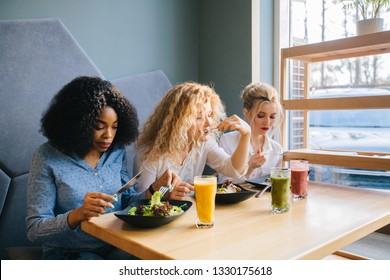 Three multi ethnic best girlfriends sitting in a row gathering to drink smoothies and eating enjoying tasty healthy food at cozy cafe. Multi-racial, difference cultures friendship concept.