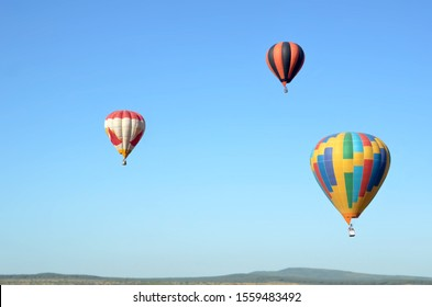 Three multicolored balloons fly in the clear blue sky above the tops of the mountains in Crimea.