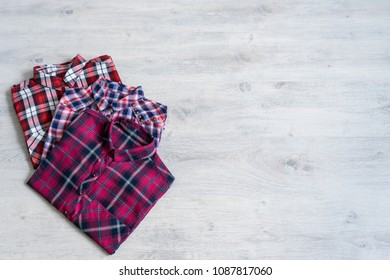Three multi-colored checkered women's shirts lying neatly folded on a light wooden background