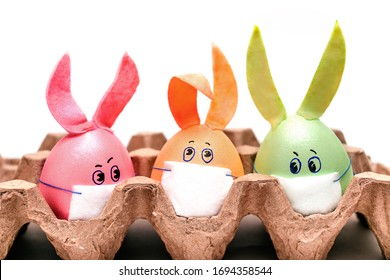Three multicolored Easter eggs with painted eyes, rabbit ears and protective masks are in an egg container. Coronavirus epidemic concept. Concept celebrating Easter in self-isolation and quarantine