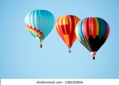 Three multicolored hot air balloons in blue sky