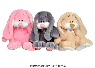 Three multi-colored plush rabbit isolated on white background. Soft toy bunnies sitting in a row.
