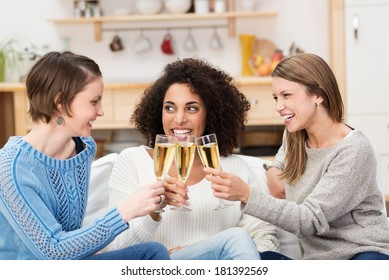 Three multiethnic attractive young women celebrating at home with champagne toasting each other as they laugh and smile