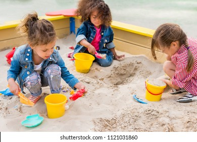 three multiethnic little children playing with plastic scoops and buckets in sandbox at playground