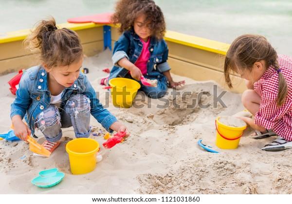 drei multiethnische Kleinkinder, die auf dem Spielplatz mit Plastikschaufeln und Eimern in Sandkasten spielen