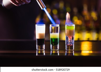 Three multi-layer burning cocktail. The bartender ignites them lighter.