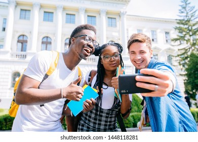 Three multiracial friends students having fun and joking together making common selfie for social networks, hipster girl and two boys in casual wear taking photos on smartphone enjoying time together.