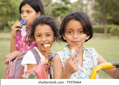 three multiracial little girls eating ice cream in the play ground