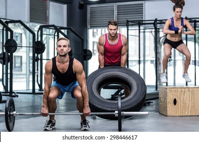 Three muscular athletes lifting and jumping at the crossfit gym