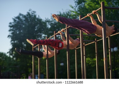 Three muscular men making workout on horizontal bar in the the street