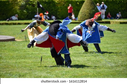 Three musketeers saluting with their swords during a performance held in the gardens of Château de Vaux-le-Vicomte, France.