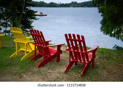 Three Muskoka chairs on a sandy beach facing a calm blue lake. The chairs are red and yellow