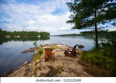 Three Muskoka chairs sitting on a rock formation facing a calm lake. Across the water are cottages nestled among green trees. The sky is cloudy