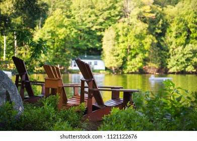 Three Muskoka chairs sitting on a wood dock facing a calm lake. Across the water is a white cottage nestled among green trees. There is a boat dock on the water in front of the cottage.