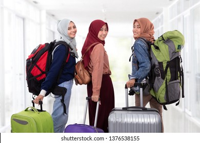 three muslim woman going vacation holding suitcase and backpack together