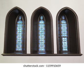 Three narrow stained glass windows with black Gothic framing