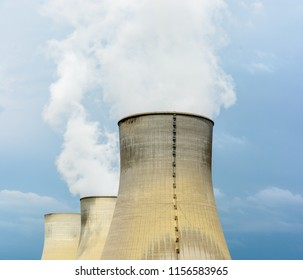 Three natural draft cooling towers of a nuclear power plant releasing clouds of water vapor against a dark stormy sky.