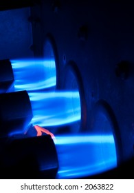 Three natural gas burners firing brilliant blue flames into an active furnace, the core of a central heating system. Orange pilot light/filament at lower left ensures burners stay lit.