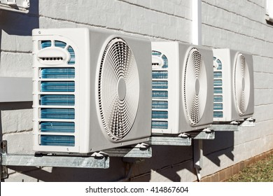 Three newly installed airconditioning units mounted on exterior wall