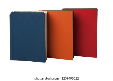 Three notebooks are standing on the edge diagonally: blue, orange, red. Business concept. White background.