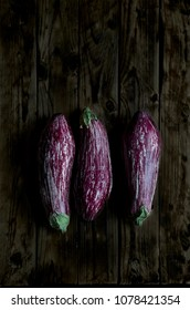 Three Nubia eggplants over a rustic wooden table in a darkness ambient.