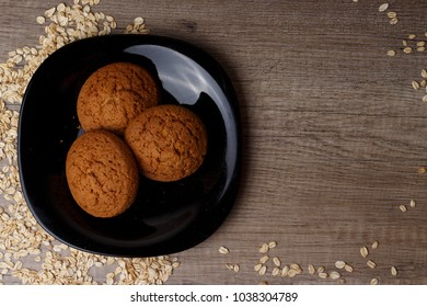 three oatmeal cookies lie on a black plate, beside scattered oatmeal, there is a place under the text