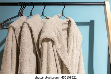 Three off white bath gown hanged on the rack with blue background.