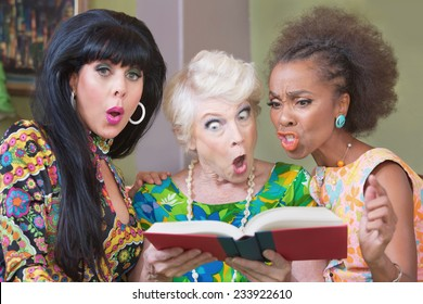 Three offended mature women reading a hardcover book