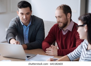 Three office workers discussing main tasks