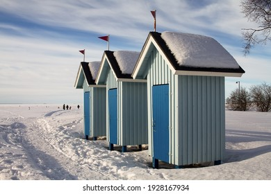 Three old beach huts stand empty on a beautiful winter day. People are walking on the ice and not going swimming.