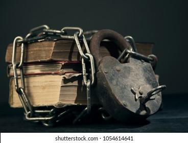 Three old books chain lock concept toning shot
