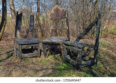 Three old burned and destroyed wooden chairs in the backyard