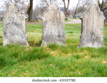 Three old graves stones on a cloudy day. They are made from limestone, and covered with moss and lichen. No text is visible. There is room for text in the grass at the bottom.