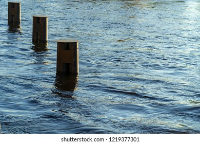 three old iron columns of a support closeup in water of the river