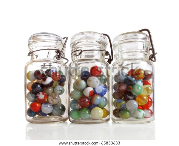 Three old jars contain a collection of colorful antique marbles