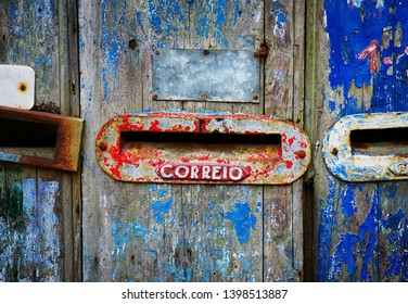 Three old mailboxes in an damaged wooden door with peeling blue paint. Correio means Mail.