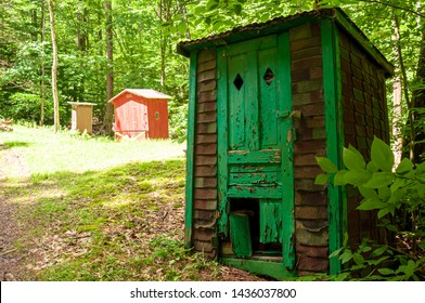 Three old outhouses in the woods in Deerfield Township, Pennsylvania, USA on a sunny summer day