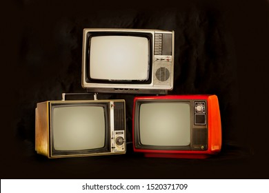 Three old retro television pile on a black background.