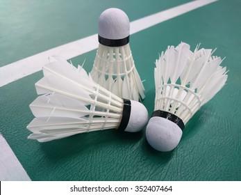Three old shuttlecocks on the badminton court