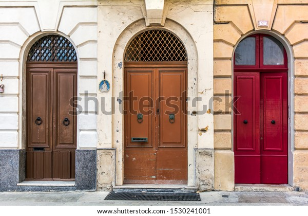 three-old-wooden-arched-doors-600w-15302