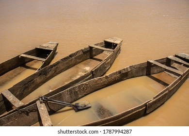 Three old wooden boats docked on a dirty river. One of the boats has two shovels in it.