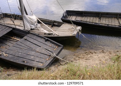 Three old wooden boats moored on the river.