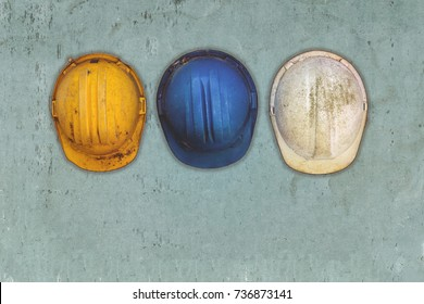 Three old and worn construction helmets hanging on a wall