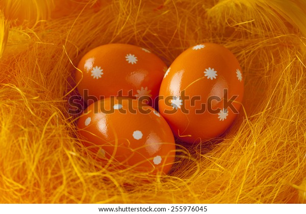 Three orange Easter eggs in nest