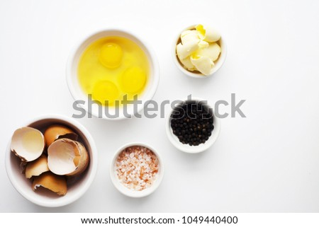 Three organic brown eggs in white bowl on white background. Used eggs shells in second bowl and shot top down. Pink salt and black pepper corns.