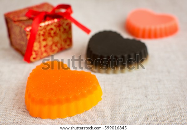 Three original handmade soaps shaped like hearts. Red gift box on the background.